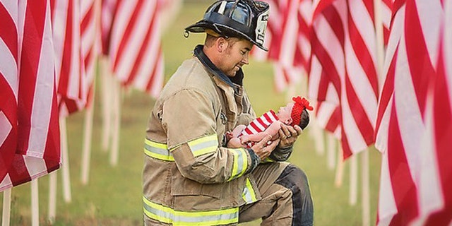 Dressed in uniform, Captain Kevin Phillips with the Charlotte Fire Department is seen holding daughter Parker Jean Phillips in between a row of American flags.