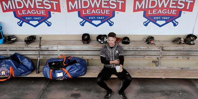 Quad Cities River Bandits infielder Trey Dawson sits in the dugout before a Class-A Midwest League baseball game against the Cedar Rapids Kernels in Cedar Rapids, Iowa. (AP Photo/Charlie Neibergall)