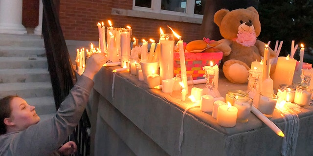 Julia Bodrero putting her candle onto a memorial following a vigil for 5-year-old Elizabeth Shelley on Monday.