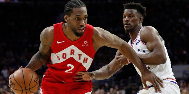 Toronto Raptors' Kawhi Leonard, left, drives against Philadelphia 76ers' Jimmy Butler, right, during the second half of Game 4 of a second-round NBA basketball playoff series, Sunday, May 5, 2019, in Philadelphia. The Raptors won 101-96. (AP Photo/Chris Szagola)