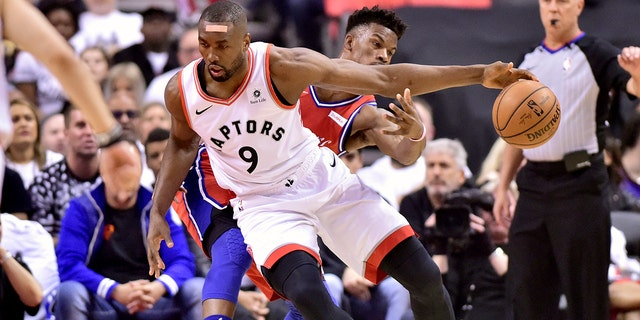 Philadelphia 76ers guard Jimmy Butler (23) fails to steal the ball as Toronto Raptors center Serge Ibaka (9) moves the ball down the court during first half NBA Eastern Conference semifinal action in Toronto on Sunday, May 12, 2019. (Frank Gunn/The Canadian Press via AP)