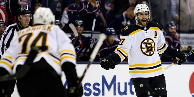 Boston Bruins forward Patrice Bergeron, right, celebrates his goal against the Columbus Blue Jackets with forward Jake DeBrusk during the first period of Game 4 of an NHL hockey second-round playoff series in Columbus, Ohio, Thursday, May 2, 2019. (AP Photo/Paul Vernon)