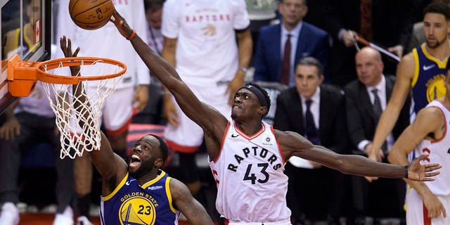 Toronto Raptors forward Pascal Siakam (43) blocks a shot by Golden State Warriors forward Draymond Green (23) during the second half of Game 1 of basketball's NBA Finals, Thursday, May 30, 2019, in Toronto. (Associated Press)