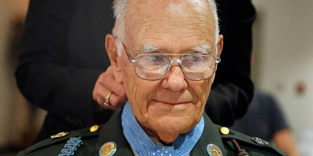 Robert Maxwell's Medal of Honor is fastened by Mary Spilde, president of Lane Community College, at a ceremony dedicating the Maxwell Student Veteran Center in his in Eugene, Ore. (AP Photo/The Register-Guard, Paul Carter)