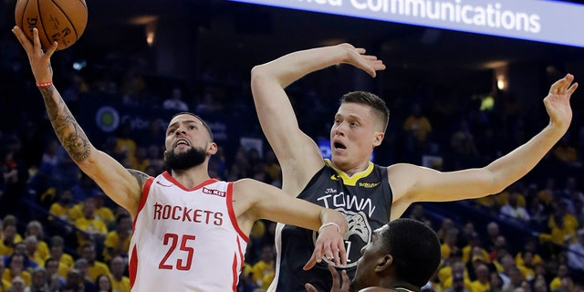 Houston Rockets' Austin Rivers (25) drives to the basket as Golden State Warriors' Jonas Jerebko, right rear, defends during the first half of Game 2 of a second-round NBA basketball playoff series in Oakland, Calif., Tuesday, April 30, 2019. (Associated Press)