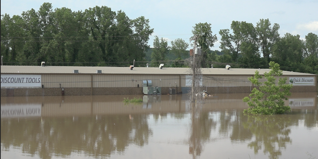 The flooding has already submerged Fort Smith business Quick Discounts near a bridge over the river connecting Fort Smith and Van Buren.