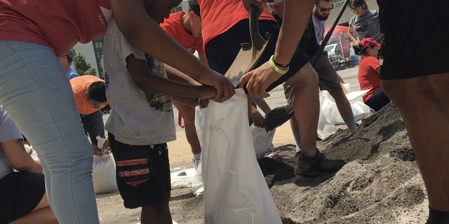 Four-year-old Jeremiah helps load sandbags in Fort Smith