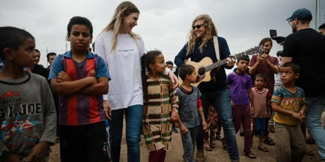 "Bethel Music worship leaders Bethany Wohrle and Sean Feucht play music with refugees as part of the ""Light A Candle Project."""