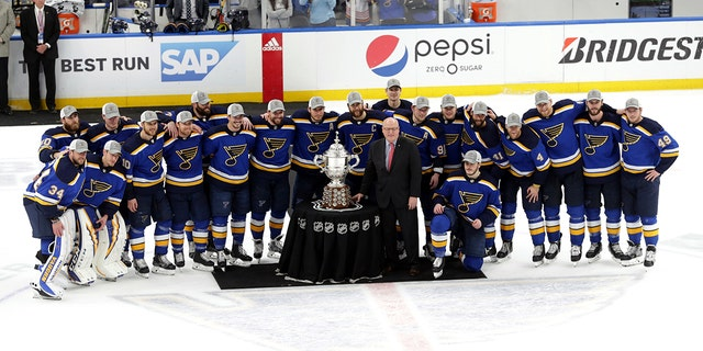 Members of the St. Louis Blues are presented the Clarence S. Campbell Bowl by NHL deputy commissioner Bill Daly after defeating the San Jose Sharks in Game 6 of the NHL hockey Stanley Cup Western Conference final series on Tuesday. (Associated Press)