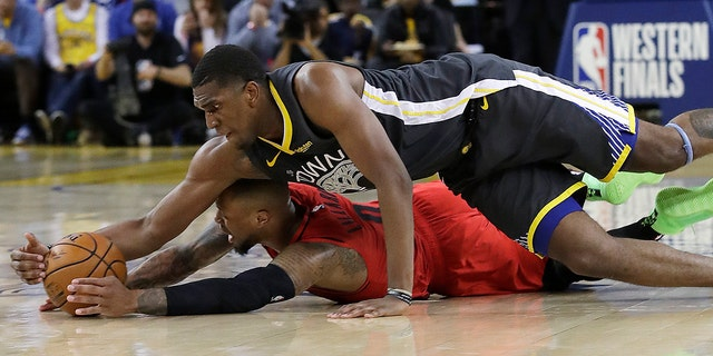 Golden State Warriors core Kevon Looney, top, reaches for a turn over Portland Trail Blazers ensure Damian Lillard during a second half of Game 2 of a NBA basketball playoffs Western Conference finals in Oakland, Calif., on Thursday. (Associated Press)