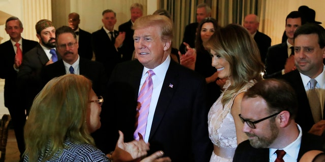President Donald Trump joined by first lady Melania Trump arrive to attend a National Day of Prayer dinner gathering of faith leaders from the interfaith community in the State Dining Room of the White House in Washington, Wednesday, May 1, 2019. (AP Photo/Manuel Balce Ceneta)