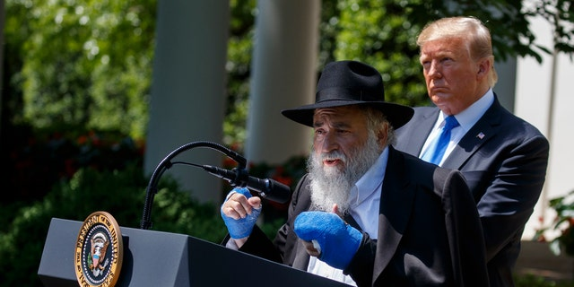 President Donald Trump looks on as Rabbi Yisroel Goldstein, survivor of the Poway, Calif synagogue shooting, speaks during a National Day of Prayer event in the Rose Garden of the White House, Thursday, May 2, 2019, in Washington. (AP Photo/Evan Vucci)