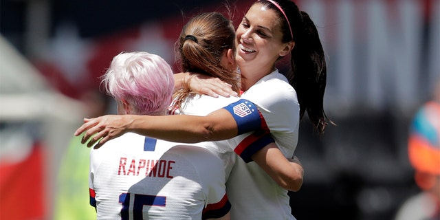 Unites States forward Megan Rapinoe (15) and forward Alex Morgan (13) hugging teammate forward Tobin Heath, center, after she scored a goal against Mexico. (AP Photo/Julio Cortez)