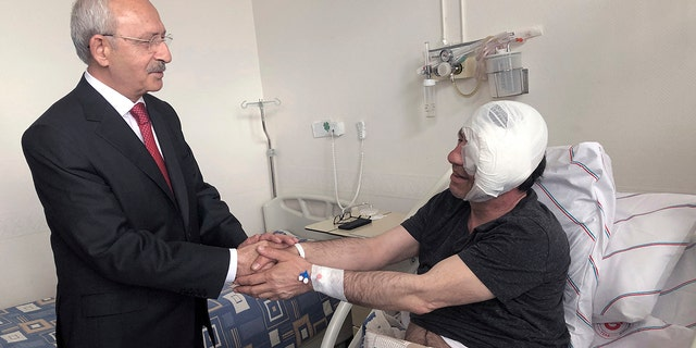 Yavuz Selim Demirag, a Turkish journalist critical of President Recep Tayyip Erdogan's government and its nationalist allies, shakes hands with visiting Kemal Kilicdaroglu, the leader of Turkey's main opposition Republican People's Party, second left, as he rests in a hospital bed in Ankara, Turkey, Saturday, May 11, 2019. Yenicag newspaper says Saturday columnist Demirag was beaten by a group of about five or six people with baseball bats outside his home after appearing on a TV show late Friday.(AP Photo/Burhan Ozbilici)