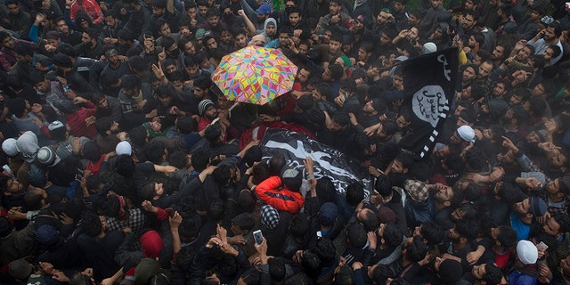 Kashmiri villagers carry the body of Zakir Musa, a top militant commander linked to al-Qaida, as it rains during his funeral procession in Tral, south of Srinagar, Indian controlled Kashmir, Friday, May 24, 2019. (AP Photo/Dar Yasin)