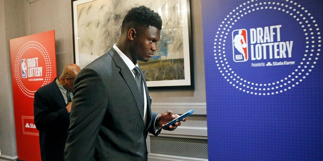 Zion Williamson checks his phone as he arrives for the NBA draft lottery in Chicago Tuesday night. (AP Photo/Nuccio DiNuzzo)