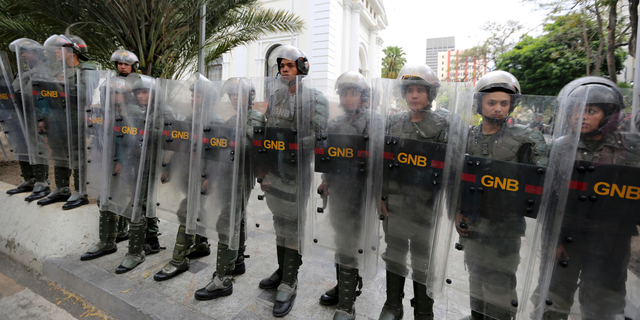 Venezuelan Bolivarian National guards officers form a cordon around the National Assembly building as the opposition-controlled congress met to discuss a move that could provide political cover for greater international involvement in the nation's crisis, in Caracas, Venezuela, Tuesday, May 7, 2019. Military police prevented journalists from entering the National Assembly, and some reporters were harassed by government supporters outside the building. (AP Photo/Fernando Llano)