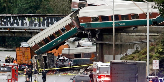 In this Dec. 18, 2017, file photo, cars from an Amtrak train lay spilled onto Interstate 5 alongside smashed vehicles as some train cars remain on the tracks above in DuPont, Wash.