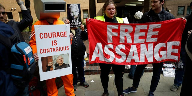 Protesters outside court as Julian Assange will appear to be sentenced on charges of jumping British bail seven years ago, in London, Wednesday May 1, 2019. Founder of WikiLeaks whistleblower website, Assange faces a separate court hearing later, on a U.S. extradition request, after being arrested at the Ecuadorian embassy April 11, when his political asylum was withdrawn.(AP Photo/Matt Dunham)