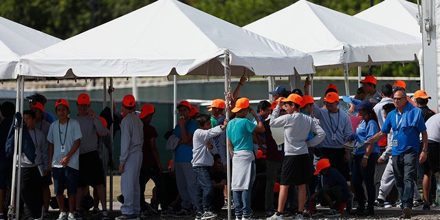 Migrant children stand outside the Homestead Temporary Shelter for Unaccompanied Children in Homestead, Fla, in May. The U.S. government is providing long-distance video counseling to teens housed at the country's largest migrant detention center as officials struggle to accommodate increasing numbers of minors illegally crossing the U.S.-Mexico border. (AP)