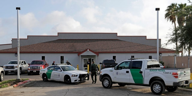 In this June 23, 2018 file photo, a U.S. Border Patrol Agent walks between vehicles outside the Central Processing Center in McAllen, Texas.