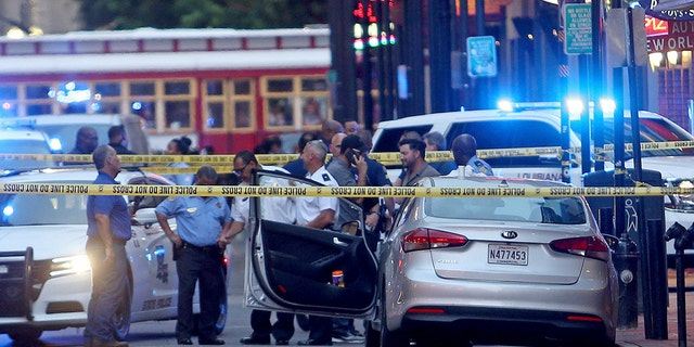 Investigators look at a Kia Forte with a shattered driver's window after a Louisiana state trooper shot the driver of the car on tourist-filled Bourbon Street in the French Quarter of New Orleans, on Thursday, May 30, 2019. (Associated Press)