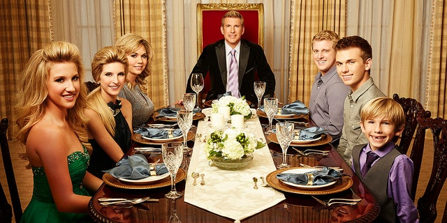 Savannah Chrisley, Lindsie Chrisley Campbell, Julie Chrisley, Todd Chrisley, Kyle Chrisley, Chase Chrisley, and Grayson Chrisley pose for a press photo for