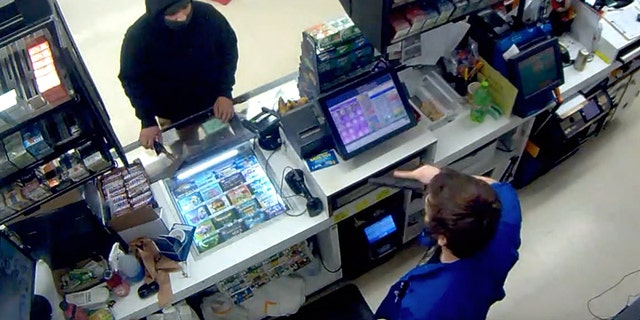 Image from surveillance video showing aconvenience store in Oregon pulling out a gun on a masked would-be robber who had a hatchet.