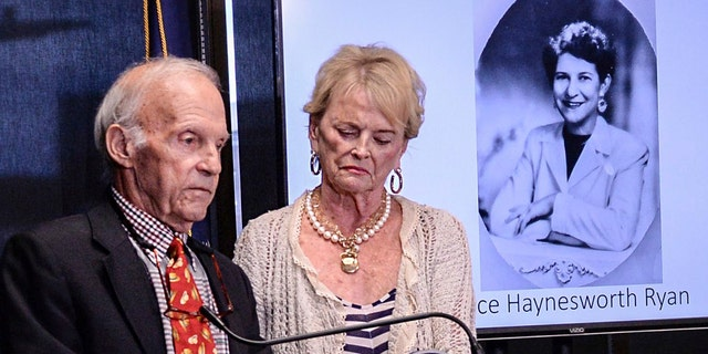 Joe Ryan, left, of Greenville stands with his wife near a photo of his late mother Alice Haynesworth Ryan, during a city police announcement of an arrest in the 1988 cold case homicide.