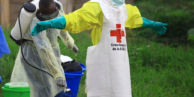 Sept 9, 2018: A health worker sprays disinfectant on his colleague after working at an Ebola treatment center in Beni, eastern Congo.