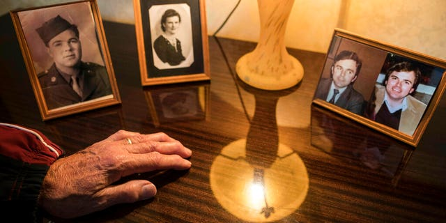 Andre Gantois's hand rests by the photos of his parents, Wilburn Henderson, left, and mother, Irene Gantois, and at the right a split portrait showing Andre Gantois, left, and his brother Allen Henderson, as young men.