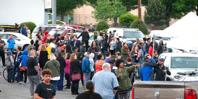 Students gather outside Parkrose High School during a lockdown after a man armed with a gun was wrestled to the ground by a staff member. (Dave Killen/The Oregonian via AP)