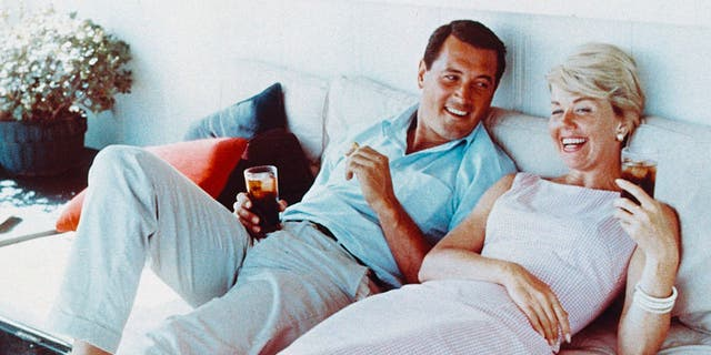 Rock Hudson (1925-1985), US actor, wearing white trousers and a light blue short-sleeved shirt, and Doris Day, US singer and actress, in a pink gingham dress, both reclining on a sofa, laughing and holding drinks, circa 1960. (Photo by Silver Screen Collection/Getty Images)
