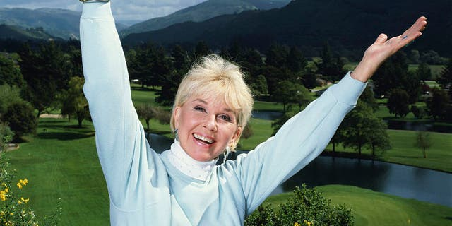 Doris Day in an exuberant pose with her arms outstretched, circa 1990. (Photo by Terry O'Neill/Iconic Images/Getty Images)