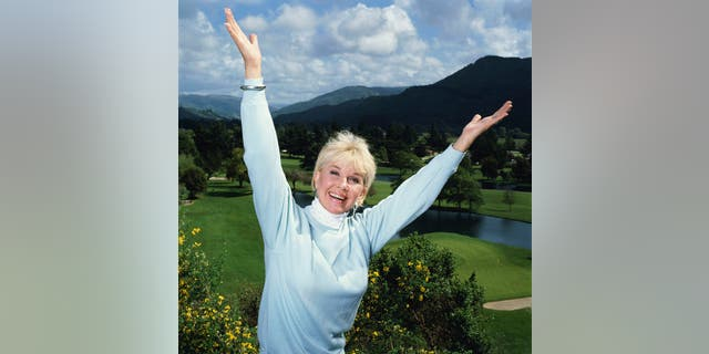 American singer and actress Doris Day in an exuberant pose with her arms outstretched, circa 1990. (Photo by Terry O'Neill/Iconic Images/Getty Images)