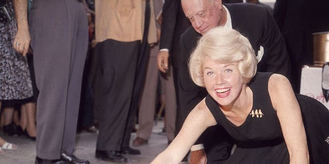 Doris Day in 1961, smiling as she signs her name in cement by her handprints, in front of Mann's (formerly Grauman's) Chinese Theater, on Hollywood Boulevard, Hollywood, California. (Photo by Hulton Archive/Getty Images)