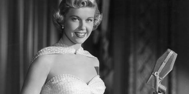 "Doris Day smiling as she stands behind a microphone, from director Michael Curtiz's film, ""Young Man with a Horn."""