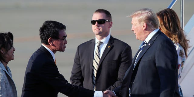 U.S. President Donald Trump, right, is greeted by Japanese Foreign Minister Taro Kono, left, on Trump's arrival at the Haneda International Airport Saturday, May 25, 2019, in Tokyo. (Associated Press)