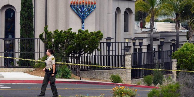"""FILE - In this Sunday, April 28, 2019 file photo, a San Diego county sheriff's deputy stands in front of the Poway Chabad Synagogue in Poway, Calif. The gunman who attacked the synagogue last week fired his semi-automatic rifle at Passover worshippers after walking through the front entrance that synagogue leaders identified last year as needing improved security. The synagogue applied for a federal grant to better protect that area. The money, $150,000, was approved in September but only arrived in late March. """"Obviously we did not have a chance to start using the funds yet,"""" Rabbi Scimcha Backman told The Associated Press. (AP Photo/Denis Poroy, File)"""