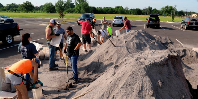 Volunteers fill sandbags at the soccer field parking lot in Chaffee Crossing, Ark., Saturday, May 25, 2019, for distribution throughout the area for flood-prone areas around homes.