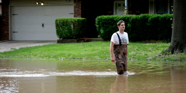 Grant Scepanski walking through his Indian Springs Estates neighborhood in Broken Arrow, Okla., amid the floods last Friday. (Mike Simons/Tulsa World via AP)