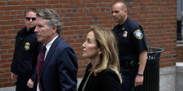 Actress Felicity Huffman arrives with her brother Moore Huffman Jr., at federal court Monday, May 13, 2019, in Boston, where she pleaded guilty.