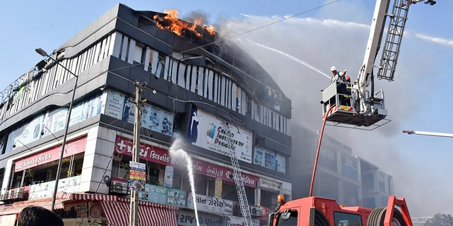 Firefighters work to douse flames on a building in Surat, in the western Indian state of Gujarat, Friday, May 24, 2019.
