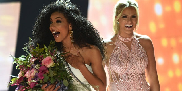 Miss North Carolina Cheslie Kryst, left, gets crowned by last year's winner Sarah Rose Summers, right, after winning the 2019 Miss USA final competition in the Grand Theatre in the Grand Sierra Resort in Reno, Nev., on Thursday, May 2, 2019. (Jason Bean/The Reno Gazette-Journal via AP)