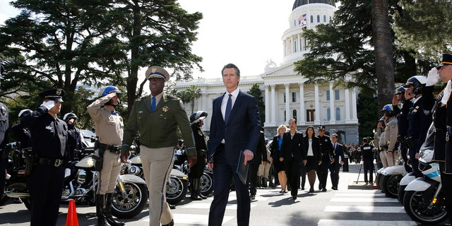 Gov. Gavin Newsom, right, and California Highway Patrol Commissioner Warren Stanley, left, pass a line of law enforcement officers as they walk to the California Peace Officers Memorial, Monday, May 6, 2019, in Sacramento, Calif.