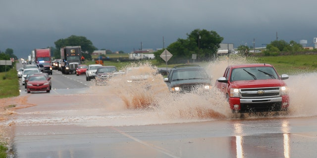 Vehicles drive through floodwater on US Highway 66 following heavy rains Tuesday, May 21, 2019, in El Reno, Okla.