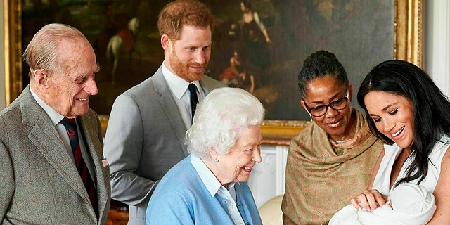 In this image made available by SussexRoyal on Wednesday, May 8, 2019, Britain's Prince Harry and Meghan, Duchess of Sussex, joined by her mother Doria Ragland, show their new son to Queen Elizabeth II and Prince Philip at Windsor Castle, Windsor, England. Prince Harry and Meghan have named their son Archie Harrison Mountbatten-Windsor. (Chris Allerton/SussexRoyal via AP)