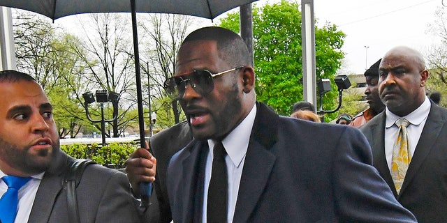 Musician R. Kelly, center, arrives at the Leighton Criminal Court building for a hearing Tuesday, May 7, 2019, in Chicago.