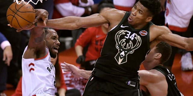 Milwaukee Bucks forward Giannis Antetokounmpo (34) blocks a dunk attempt by Toronto Raptors forward Kawhi Leonard, left, during the second half of Game 6 of the NBA basketball playoffs Eastern Conference finals Saturday, May 25, 2019, in Toronto.