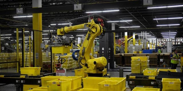 A 6-axis robotic arm picks up sorting containers at the Amazon fulfillment center in Baltimore, Maryland.